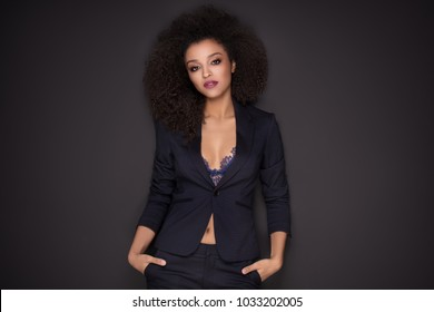 Elegant beautiful business woman after work, posing over black background. Girl with afro hairstyle and glamour makeup.