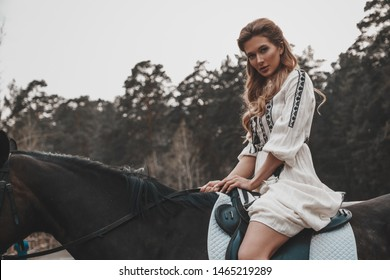Elegant and beautiful magnificent young woman wearing the dress is holding reins and riding a horse. An attractive rider is posing outdoors. Summertime, nature landscape, countryside