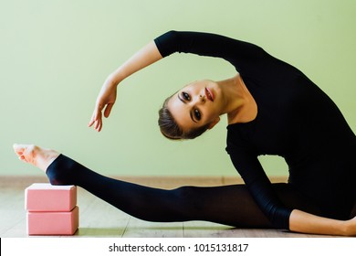 elegant beautiful modern ballet dancer girl with perfect body sits on the floor on on twine in the studio. Sexy brunette Stretching with yoga pink blocks. Make-up, hairstyle bun. Dark stockings.