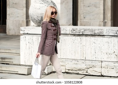 Elegant beautiful sexy blonde woman posing. She standing outside. Grey coat. Sensual model. She standing near big building. Black sunglases. Sensual baby. Hot lade. Beginer model.