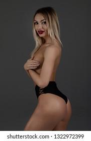 Elegant beautiful sexy blonde woman posing in studio, looking at camera.