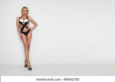 Elegant beautiful sexy young woman, model blond long hair standing on white dressed in elegant black and white swimsuit