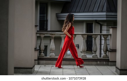 Elegant and beautiful woman portrait on rooftop, wearing long red dress. Old vintage town. She walking and looking somewhere. Black long brunette hairs. Sexy model.