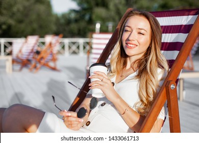Elegant beautiful woman relaxing in chair at the beach bar and drink cup of coffee. Luxary lady in glasses enjoying summer sunset alone in empty cafe outdoor.