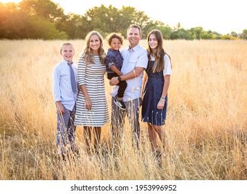 Ein elegantes und schönes Familienporträt im Freien auf einem grasbewachsenen Feld. Lächelnde und glückliche abwechslungsreiche Gruppe mit einem gemischten Rennen adoptierte Baby-Junge und zwei weitere Kinder