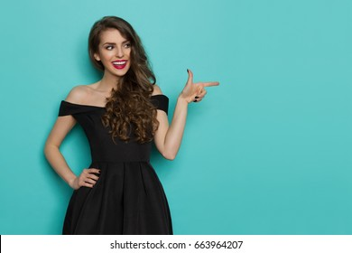 Elegant beautiful young woman in black cocktail dress is looking away, pointing and smiling. Three quarter length studio shot on turquoise background.