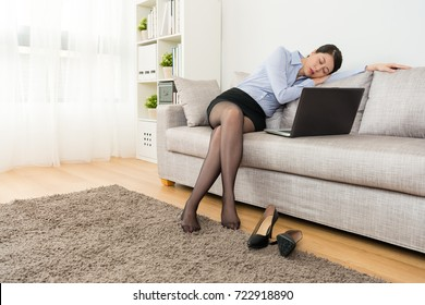 elegant beauty girl office worker using mobile laptop feeling tired sitting on sofa sleeping when she after work and back to home working.