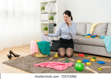 elegant beauty lady manager using mobile cell phone calling with client when she after work kneeling down on living room floor sweeping messy toys with clothing.