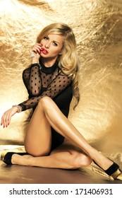 Elegant beauty posing, sitting on the floor in studio.