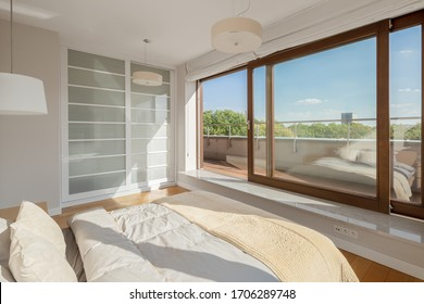 Elegant bedroom with big bed and window wall open to balcony