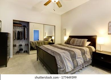 Elegant bedroom with dark brown furniture, mirror door closet