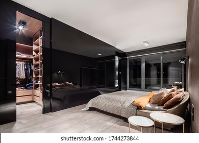 Elegant bedroom with walk in closet behind stylish, black and mirrored wall
