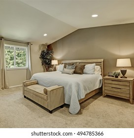 Elegant beige and brown bedroom interior with pale blue bedding, upholstery bench and decorative green tree in a pot. Northwest, USA