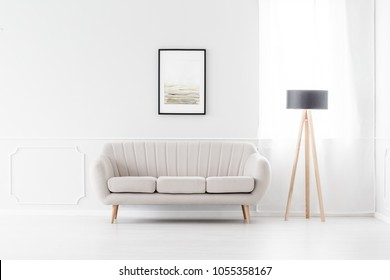 Elegant, beige sofa in an empty white interior with art above the sofa and a wooden tripod lamp by a window