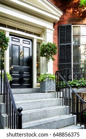 Elegant black front door exterior framed by two potted trees and flowers. Typical red brick  town house style in Beacon Hill, Boston, with black window shutters and stair railings