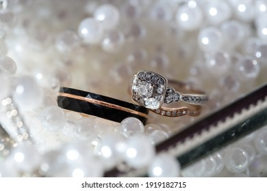 Elegant black and gold wedding rings on bed of pearls