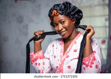 Elegant black lady looking at camera wearing a satin bonnet and floral robe, smiling in interior. Black female health and wellness indoors, skin perfection and care lifestyle.