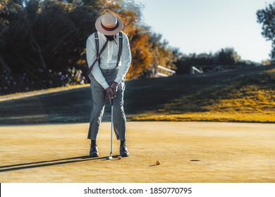 An elegant black man in a hat, white shirt and trousers with suspenders, with a cigar in his mouth is playing golf in autumn evening, on the sunset: trying to hit the ball into the closest hole
