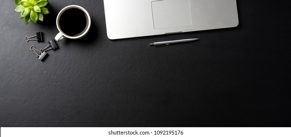 Elegant black office desktop with laptop and  cup of coffee. Top view
