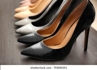 Elegant black shoes on wooden shelf, closeup