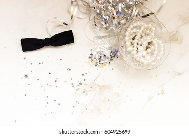 Elegant black tie, pearls, silver party decor and cocktail glasses with room for copy