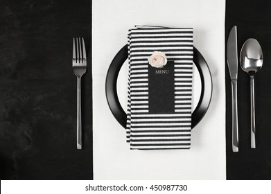 Elegant black and white table setting: plates on linen, striped napkin, blank label with rose and silverware. Top view point.