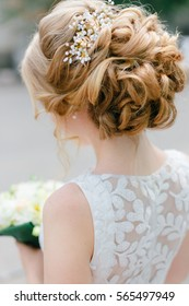 Elegant blond bride standing back with collected up do hair. Tender wedding stylish hairstyle with accessories. Fine art wedding. Light bridal morning preparation.