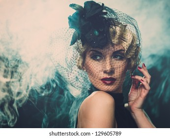 Elegant blond retro woman  wearing little hat with veil in smoke