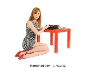 Elegant blond woman sitting on the floor typing on old typewriter on red table