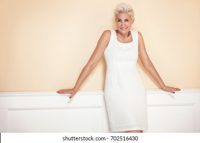 Elegant blonde beautiful adult woman smiling to the camera.
