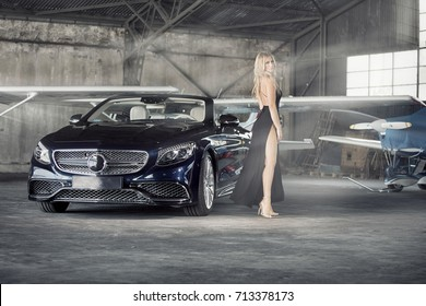 Elegant blonde beautiful woman standing by luxury car and small airplane. Girl wearing black dress.