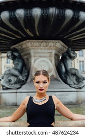 Elegant blonde in black  gown leans on a fountain.