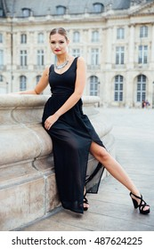 Elegant blonde in black  leans on a fountain.