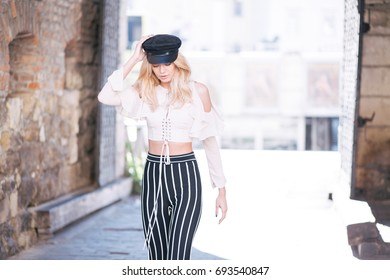 Elegant blonde in black and white clothes and hat. Architecture. Fashion. Lviv.
