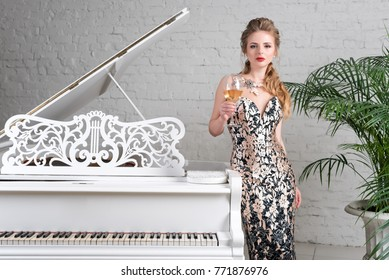 Elegant blonde lady with glass of wine in restaurant standing near white grand piano in a luxury classic interior. Beautiful sexy young woman with perfect body and pretty face make-up wearing evening
