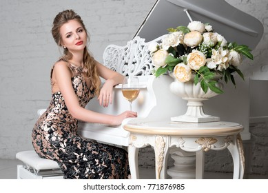 Elegant blonde lady with glass of wine in restaurant sitting near white grand piano in a luxury classic interior. Beautiful sexy young woman with perfect body and pretty face make-up wearing evening