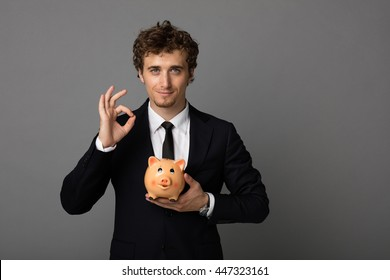 elegant blonde man in suit with blue eyes holding with confidence a piggy bank