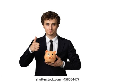 elegant blonde man in suit with blue eyes holding with confidence a piggybank