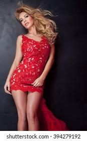 Elegant blonde woman posing in red evening dress. Studio shot. Fashionable dress.