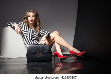 elegant blonde woman in red heels with fashion bag