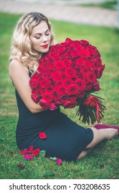 Elegant blonde woman is sitting on green lawn with big bouquet of 101 red roses