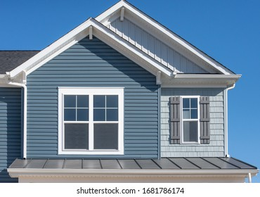 Elegant blue horizontal vinyl siding, shingle and vertical siding in a double gable roof with white decorative corbels, double sash window with matching shutter above a metal roof on a luxury home