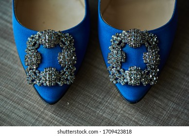 Elegant blue and silver high heel shoes for women sitting on a textured surgace.