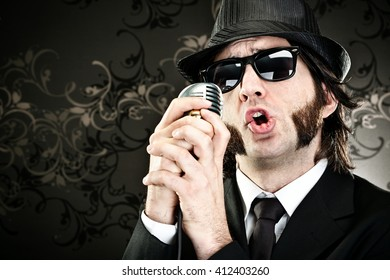 elegant boss man with sunglasses and microphone singing portrait on black background