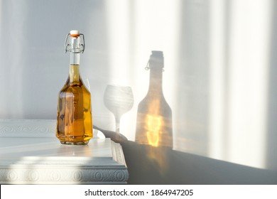 Elegant bottle with alcohol and empty glass over a vintage cabinet and a beautiful sun reflection on the wall - art concept