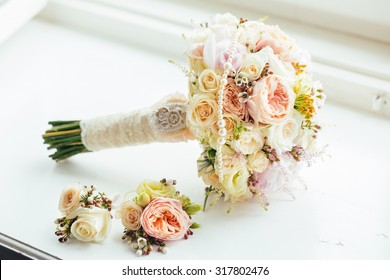Elegant bridal bouquet and groom's boutonniere of roses in light colors lying on the windowsill.