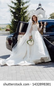 Elegant Bride with Flower Bouquet near Limousine. Sharming Cute Young Woman Dressed in White Wedding Clothing and Jewelry Diadem. Girl Standing near Black Bridal Car on Nature Background