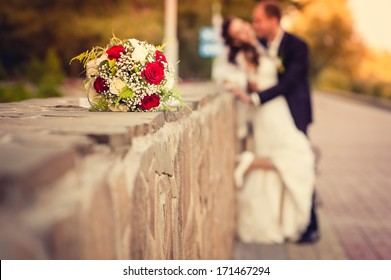 Elegant bride and groom posing together outdoors  in a park on a wedding day. Elegant bride and groom posing together outdoors on a wedding day. wedding dress. Bridal wedding bouquet of flowers.