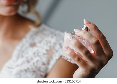 Elegant bride holding in hands a bottle of luxury perfume