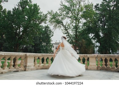 Elegant bride in puffy tulle dress with veil is dancing on terrace in old city. Woman spinning near the ancient stone walls houses. Sunny love story in the medieval town green park.